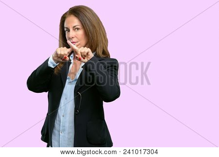 Middle age business woman annoyed with bad attitude making stop sign with hand, saying no, expressing security, defense or restriction, maybe pushing