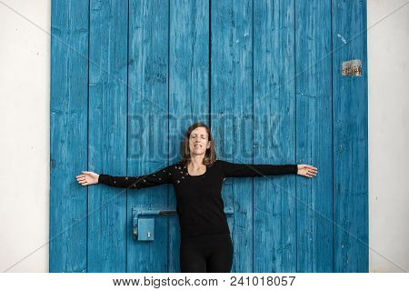 Young Woman Celebrating The Spring Sunshine Standing Meditating In The Warmth With Outstretched Arms