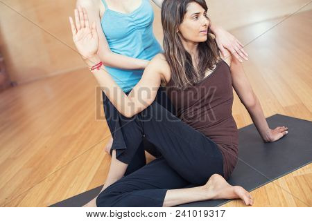 A Deep Stretch Yoga Practice: Two Multicultural Young Girls Practicing Yoga.