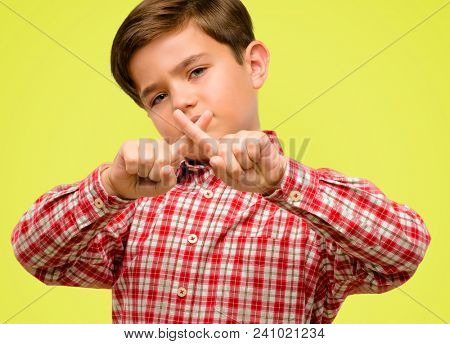 Handsome toddler child with green eyes annoyed with bad attitude making stop sign with hand, saying no, expressing security, defense or restriction, maybe pushing over yellow background