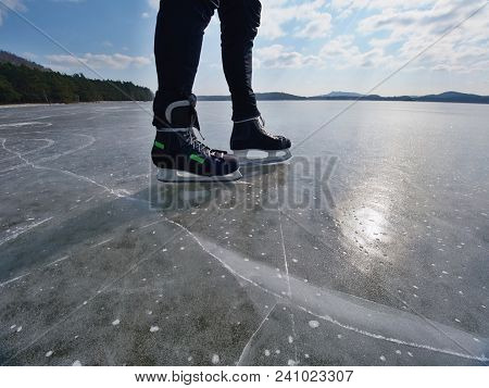 Ice Skating. An Athlete Man Stay With Hockey Ice Skates On An Frozen Lake, Winter Concept