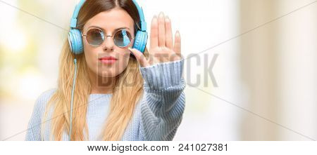 Young woman listen to music with headphone annoyed with bad attitude making stop sign with hand, saying no, expressing security, defense or restriction, maybe pushing