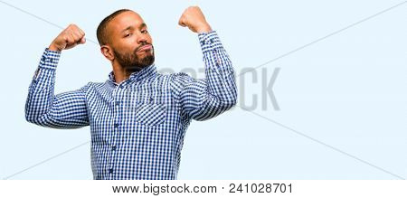 African american man with beard showing biceps expressing strength and gym concept, healthy life its good isolated over blue background