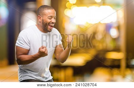 African american man with beard happy and excited celebrating victory expressing big success, power, energy and positive emotions. Celebrates new job joyful at night