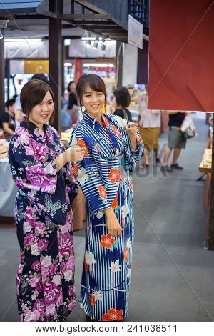 Two Young Woman Wearing Japanese Traditional Kimono Enjoy The Stroll In The Market Japan