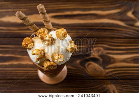 Ice Cream With Caramel And Popcorn On A  Black Background. Space For Text Or Design.