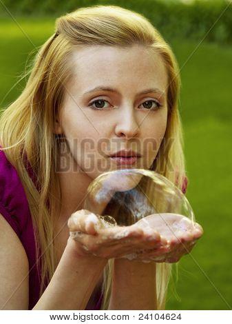 Happy girl blowing soap bubbles