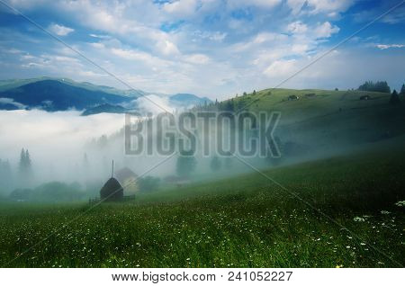 Foggy Morning Summer Mountain Landscape With Mist And Green Meadow. Rural Houses In The Fog And Dram