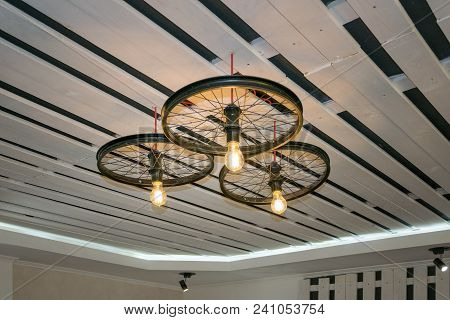 Focus On Ceiling Decorated In Black And White Colors Having Lusters In Modern Art Style. Wheels Radi