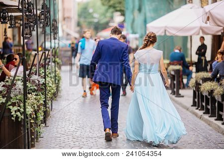 Portrait The Groom In Wedding Suit And The Bride In  Dress Walking Back Near Old Building, Old House