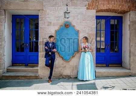Elegant Wedding Couple Gently Hugging In Sunlight In Old Courtyard In European Street. Luxury Bride