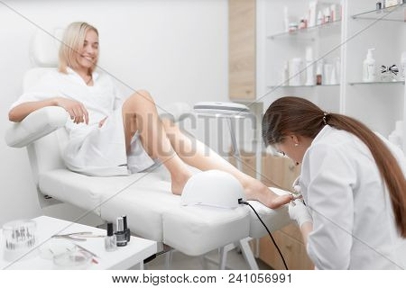 View Of Specialist In White Working In Beauty Salon, Making Pedicure For Pretty And Young Client In