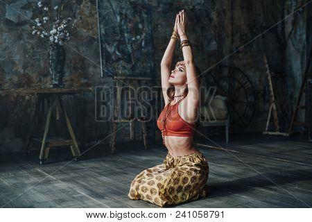 Young beautiful yogi woman in traditional clothing meditating pose