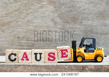 Toy Forklift Hold Letter Block E To Complete Word Cause On Wood Background