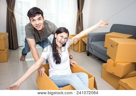 Happy Asian Couple Is Playing Together With Cardboard Boxes In New House At Moving Day.