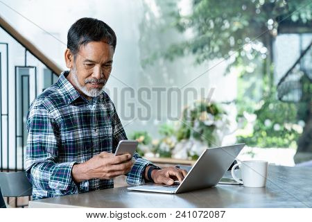 Smiling Attractive Mature Man With White, Grey Stylish Short Beard Using Smartphone Gadget Serving I