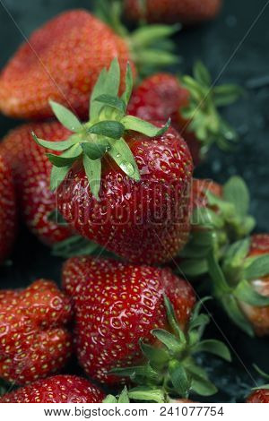 A Closeup Of Fresh Strawberries With Green Leaves. Background. Freshly Picked Red Strawberries. Grou
