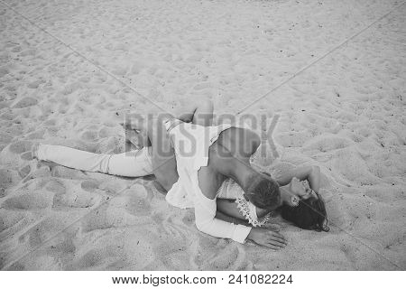 Sex On Beach Concept. Couple Full Of Desire Have Sex On Sand Of Seashore. Sensual Lovers Making Love