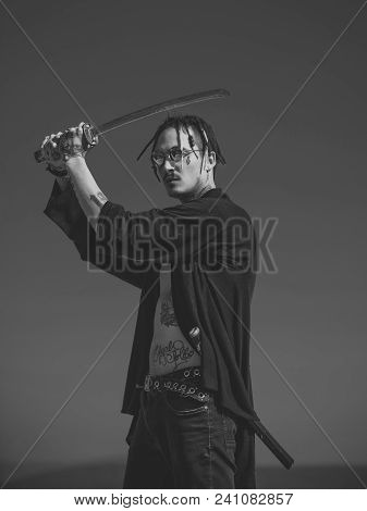 Samurai And Japan Weapon. Martial Arts Concept. Warrior With Dreadlocks And Open Clothes Showing Tat