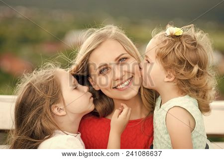 Kids Enyoj Happy Day. Woman And Girls Sit On Bench. Daughters Kiss Mother On Natural Landscape. Moth