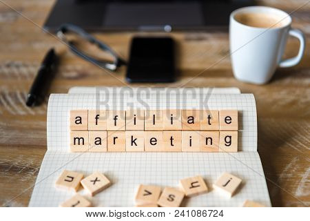 Closeup On Notebook Over Table Background, Focus On Wooden Blocks With Letters Making Affiliate Mark