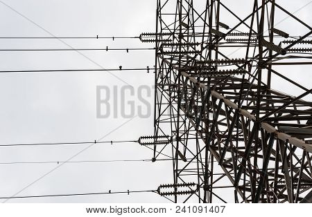 Looking Up Along Large Metal Electrical Transmission Tower With Parallel Insulators And Wires Agains