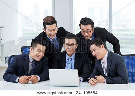 Group Of Smiling Asian Managers Wearing Classical Suits Gathered Together At Modern Office And Atten