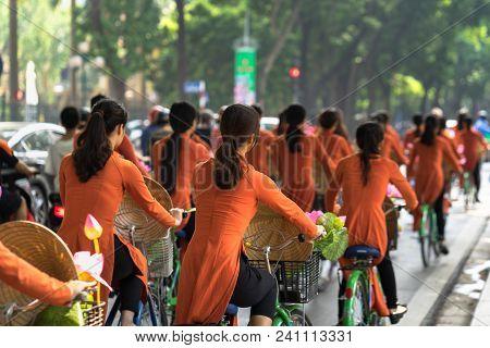 Vietnamese girls wear traditional long dress Ao Dai cycling on Hanoi street poster