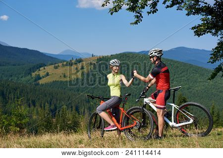Happy Couple Cyclists, Man And Woman With Bicycles, Standing On Grassy Hill Under Big Green Tree Bra