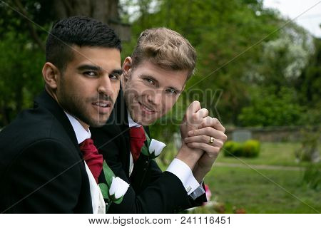 Gay Couple, Husbands Pose For Photographs In Churchyard After Their Marriage Ceremony In Village Chu