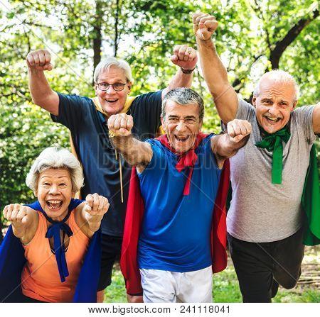 Childlike seniors wearing superhero costumes poster