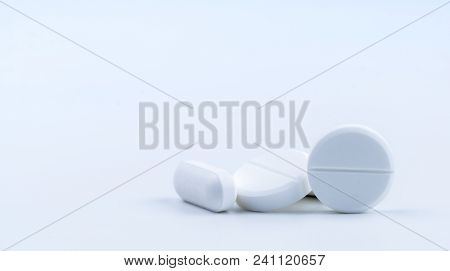 Pile Of White Round And Oblong Shape Tablet Pills Isolated On White Background. Pharmaceutical Indus