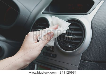 Hand with white cloth cleaning modern car interior