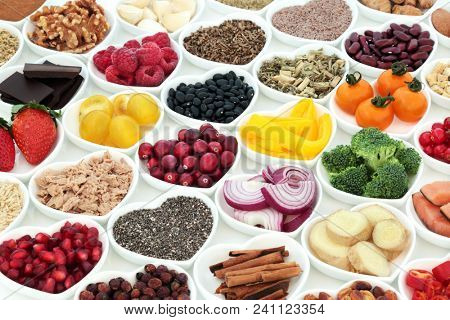 Nutrition for a healthy heart with fresh vegetables, fruit, spices, pulses, nuts, seeds, fish and medicinal herbs. Super food concept, high in omega 3 fatty acids, fibre, vitamins and antioxidants.