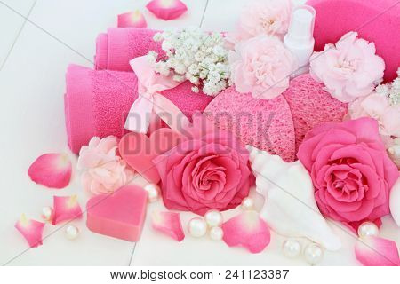 Bathroom beauty cleansing products with pink roses and carnation flowers, shell and heart shaped soap, body lotion, sponges, wash cloth and decorative pearls on white wood background.