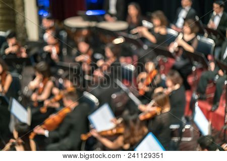 Blurred Artists Symphony Orchestra. Musician Plays A Musical Instrument On The Concert Stage.