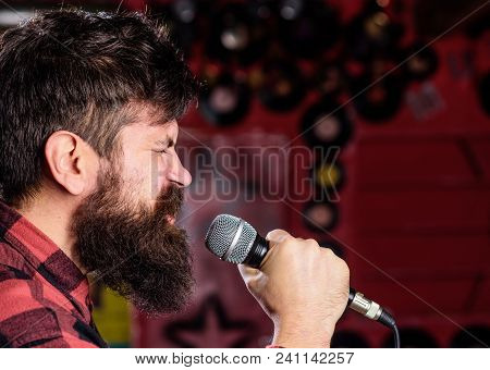 Musician With Beard And Mustache Singing Song In Karaoke. Punk Rock Concept. Man With Tense Face Hol