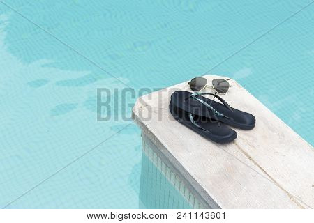 Flip-flops And Sunglasses By Blue Pool In Summer