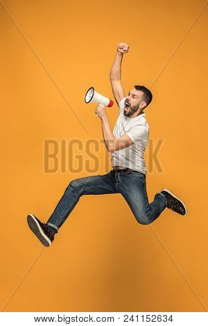 Soccer Fan Jumping On Orange Background. The Young Man As Football Fan With Megaphone Isolated On Or