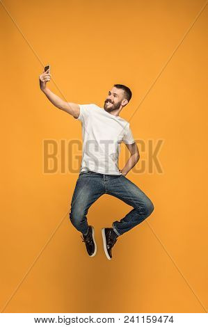 Time To Take Selfie. Full Length Of Handsome Young Man Taking Selfie While Jumping Against Orange St