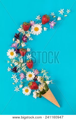 Waffle Cone With Fresh Strawberries And Flowers Blossom  Bouquets On Blue Surface. Flat Lay, Top Vie