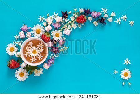 Cup Of Tea With Fresh Strawberries, Marshmallows And Flowers Blossom  Bouquets On Blue Surface. Flat