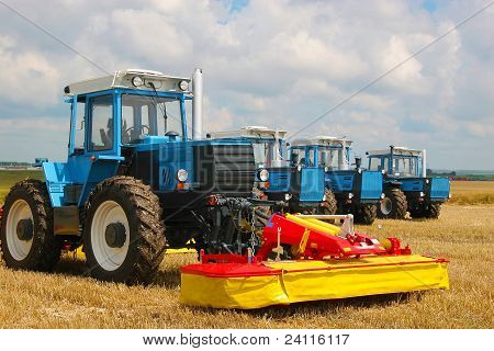 Group Of Powerful Tractors On The Field