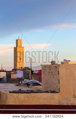 Early morning sky during sunrise with the roofs and mosque tower in Meknes, Morocco. poster