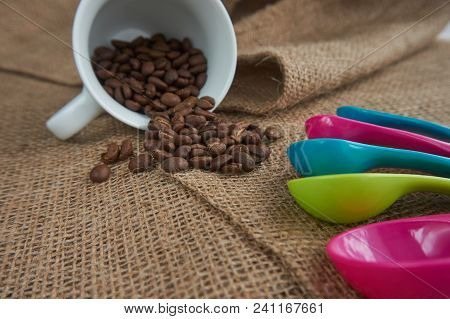 Loose roasted coffee beans, white porcelain coffee mug and color plastic dose measuring spoons on jute sack. Conceptual of recommended amount of coffee per day. Low angle selective focus and copy space poster