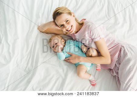 High Angle View Of Smiling Mother Laying In Bed With Infant Daughter