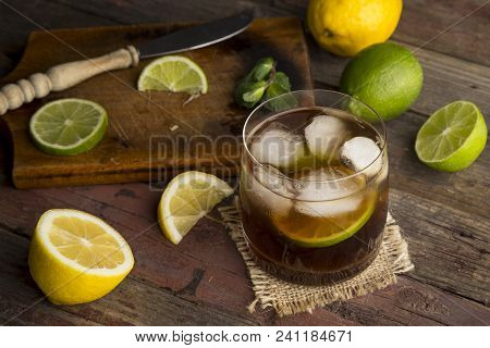 High Angle View Of A Glass Of Cuba Libre Cocktail With Rum, Coke, Lemon Juice And Ice Cubes On A Rus