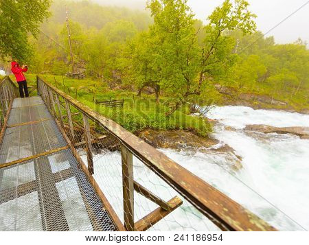 Travel And Hiking. Tourist Woman Taking Photo With Camera, Standing On Bridge, Enjoying Waterfall To