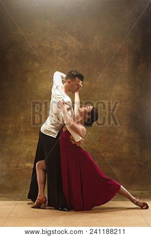 The Young Dance Ballroom Couple In Red Dress Dancing In Sensual Pose On Studio Background. Professio