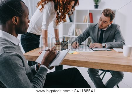 Multicultural Business Colleagues Working At Table In Office